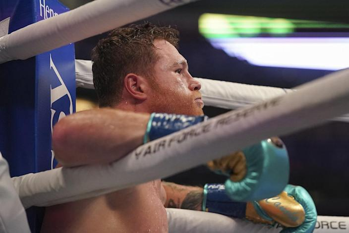 Canelo Álvarez sits down and leans his elbows on the ropes
