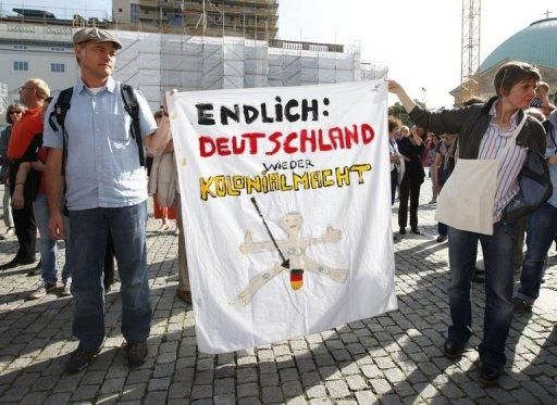"One banner at the demonstration accused Germany of reverting to a ""colonial power"""