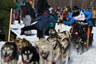 Dallas Seavey leans over for a high-five at the Iditarod Sled Dog Race start area