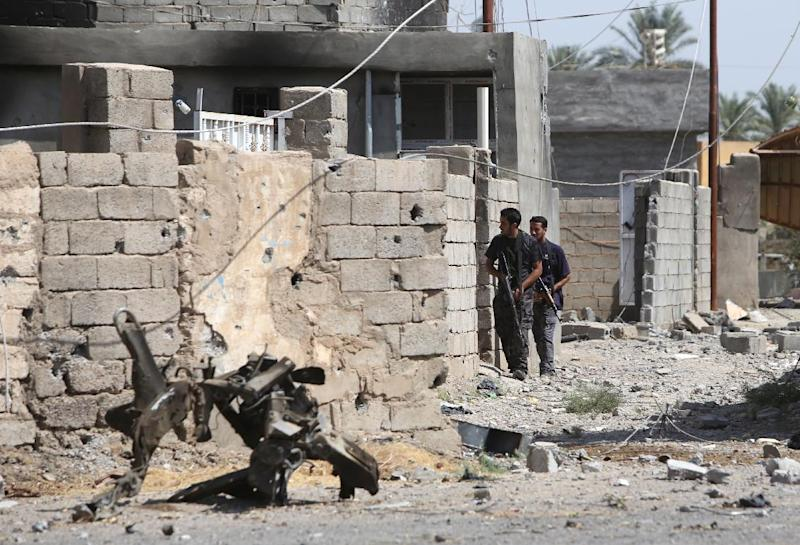 Iraqi policemen secure an area after government security forces and militia retook the city from Islamic State group jihadists in Dhuluiya on September 17, 2014 (AFP Photo/Ahmad al-Rubaye)