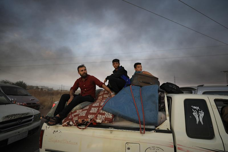 People sit on belongings at a back of a truck as they flee Ras al Ain town, Syria Oct. 9, 2019. (Photo: Rodi Said/Reuters)