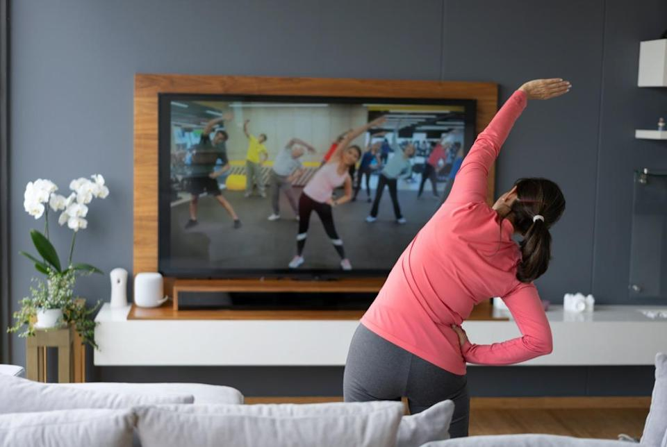 Back view of senior woman following an online stretching class looking at TV screen.