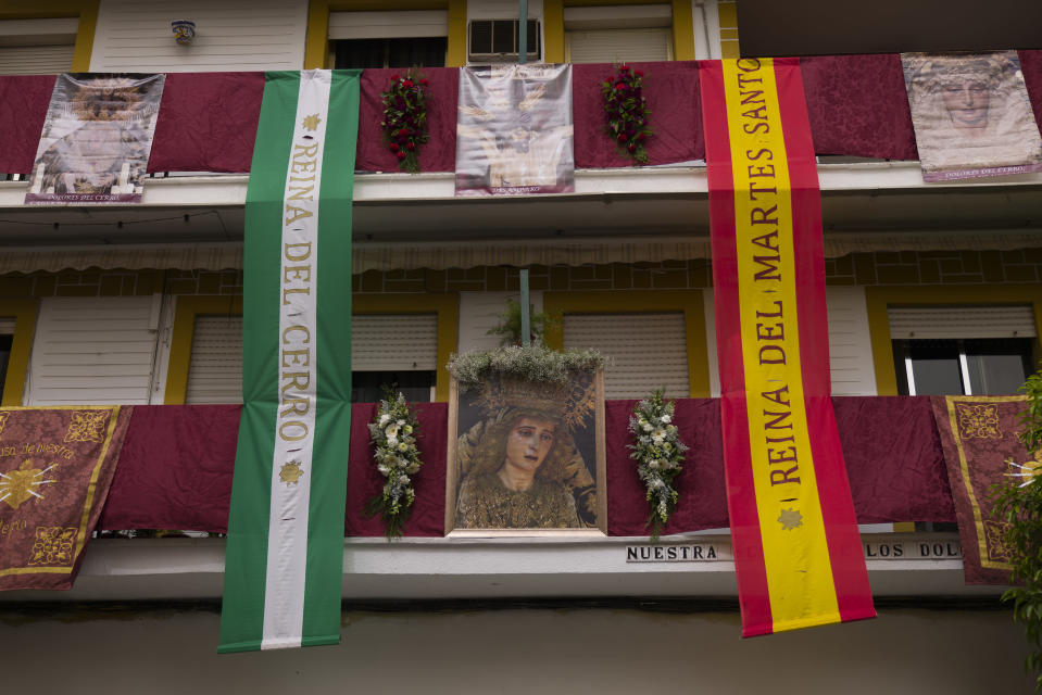 Balconies decorated with Catholic religious banners during the Holy Week in Seville, southern Spain, Tuesday, March 30, 2021. Few Catholics in devout southern Spain would have imagined an April without the pomp and ceremony of Holy Week processions. With the coronavirus pandemic unremitting, they will miss them for a second year. (AP Photo/Laura Leon)