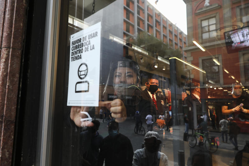 "An employee at a store posts a sign that reads in Spanish ""please wear mouth cover inside the store"" in downtown Mexico City, Tuesday, June 30, 2020. (AP Photo/Eduardo Verdugo)"