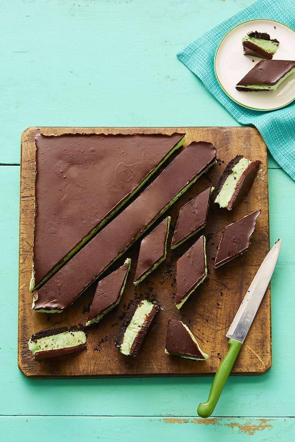 """<p>Make these mint chocolate treats to help guests cool down on a hot summer day, while satisfying their sweet tooth at the same time.</p><p><strong><em><a href=""""https://www.womansday.com/food-recipes/food-drinks/a16810585/grasshopper-bars-recipe/"""" rel=""""nofollow noopener"""" target=""""_blank"""" data-ylk=""""slk:Get the Grasshopper Bars recipe."""" class=""""link rapid-noclick-resp"""">Get the Grasshopper Bars recipe. </a></em></strong><br></p>"""