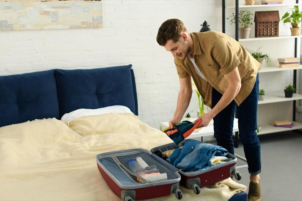 smiling man packing clothes into travel bag L