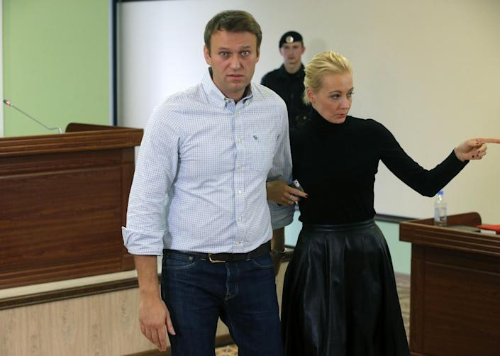 Russian opposition leader Alexei Navalny and his wife Yulia leave a court room in a Kirov court in Kirov, Russia, Wednesday, Oct. 16, 2013. A Russian courthouse in the town of Kirov set Navalny free in July, the day after he was convicted of embezzlement and sentenced to five years in prison. Navalny has appealed both the conviction and the sentence. (AP Photo/Dmitry Lovetsky)