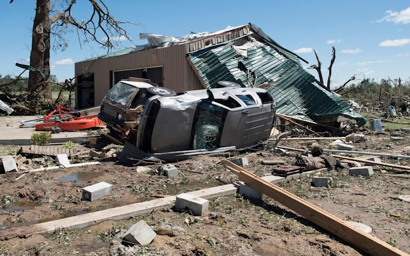 An overturned vehicle rests on the ground surrounded by debris in Canton, Texas - Credit: Tyler Morning Telegraph via AP