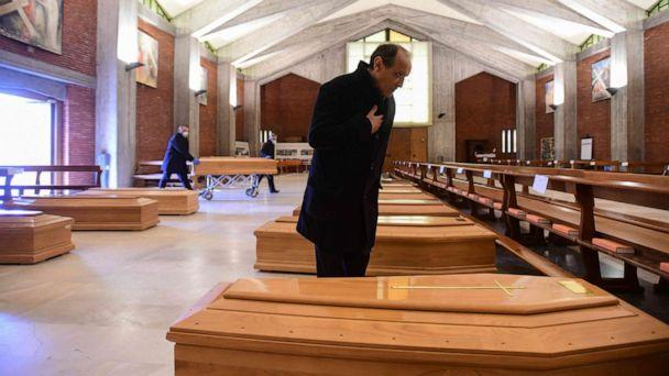 PHOTO: Parish priest of Seriate, Don Mario stands by one of the coffins stored into the church of San Giuseppe in Seriate, near Bergamo, Lombardy, on March 26, 2020, during the country's lockdown following the coronavirus pandemic. (Piero Cruciatti/AFP via Getty Images)