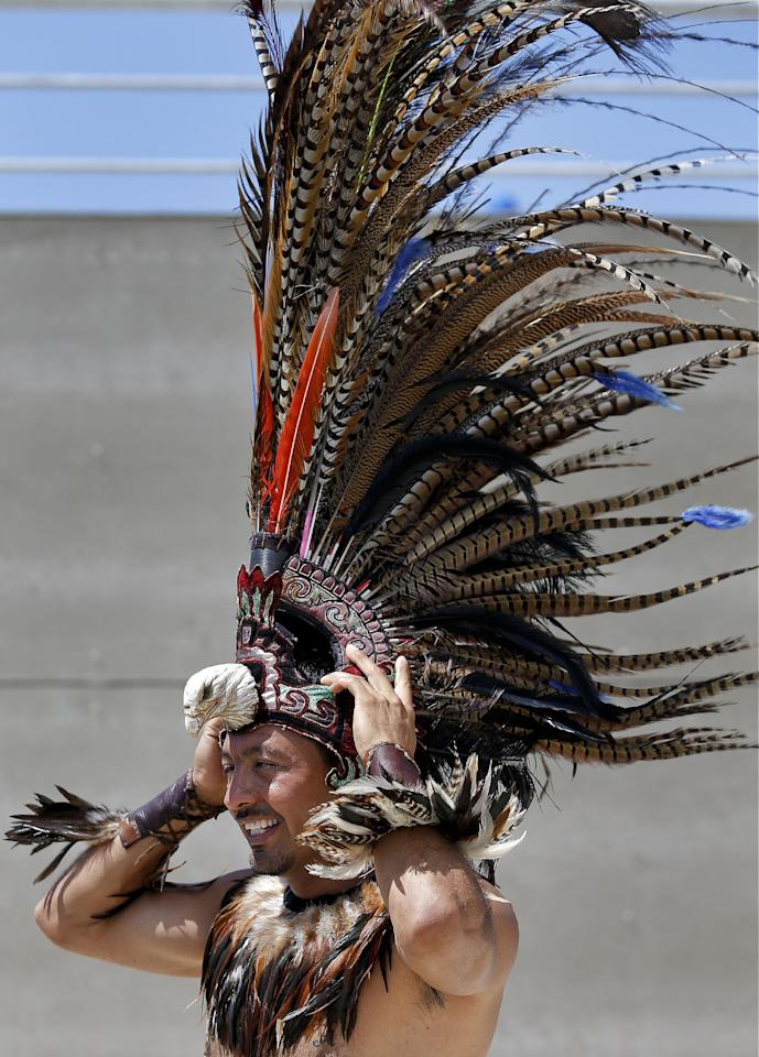 A Mexican supporter puts on Aztec plumes before the World Cup round of 16 soccer match between the Netherlands and Mexico at the Arena Castelao in Fortaleza, Brazil, Sunday, June 29, 2014. (AP Photo/Eduardo Verdugo)