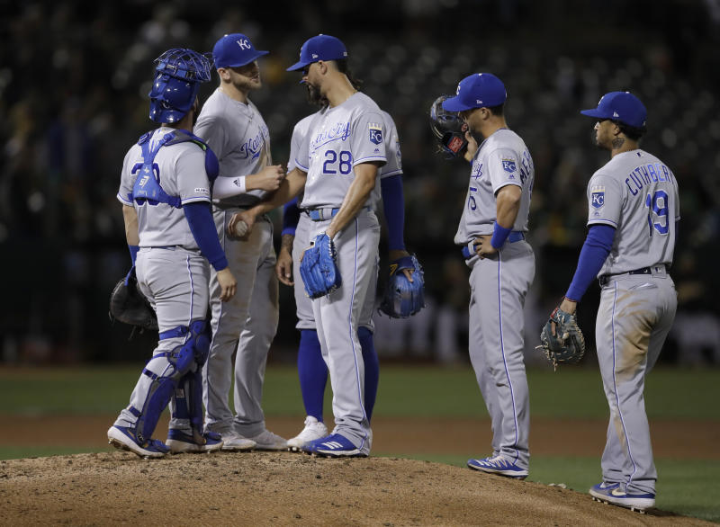 Kansas City Royals pitcher Jorge Lopez (28) speaks with players on the mound as he waits to be removed during the seventh inning of the team's baseball game against the Oakland Athletics on Tuesday, Sept. 17, 2019, in Oakland, Calif. (AP Photo/Ben Margot)
