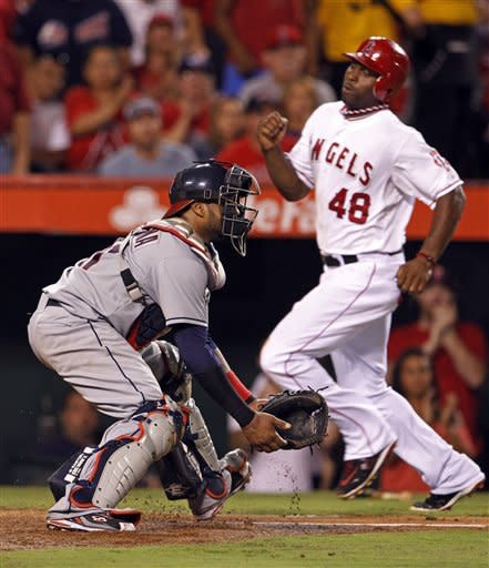 Cleveland Indians catcher Carlos Santana waits for the throw as Los Angeles Angels' Torii Hunter scores on an Albert Pujols double in the sixth inning of a baseball game in Anaheim, Calif., Tuesday, Aug. 14, 2012. (AP Photo/Reed Saxon)