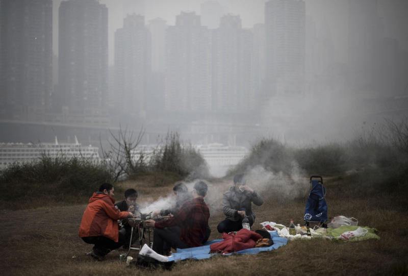 """In this photo taken Sunday Feb. 23, 2014, residents barbecue along the river bank during a hazy day in southwest China's Chongqing municipality. Xinhua said that almost all provinces in central and east China have had serious air pollution since Friday, and that Beijing and five provinces in northern and eastern China had reported """"severe smog."""" (AP Photo) CHINA OUT"""