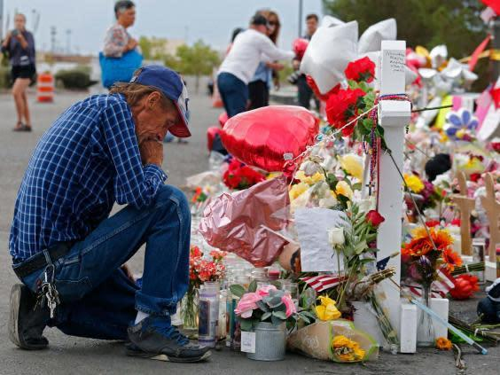 Antonio Basco kneels at a memorial for his wife Margie Reckard and other victims of the El Paso shooting (EPA)