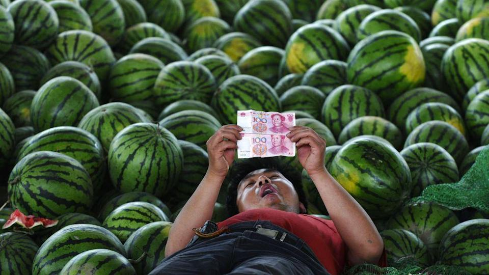 A watermelon vendor looks at yuan banknotes at a market in Changzhi, Shanxi province June 21, 2010.