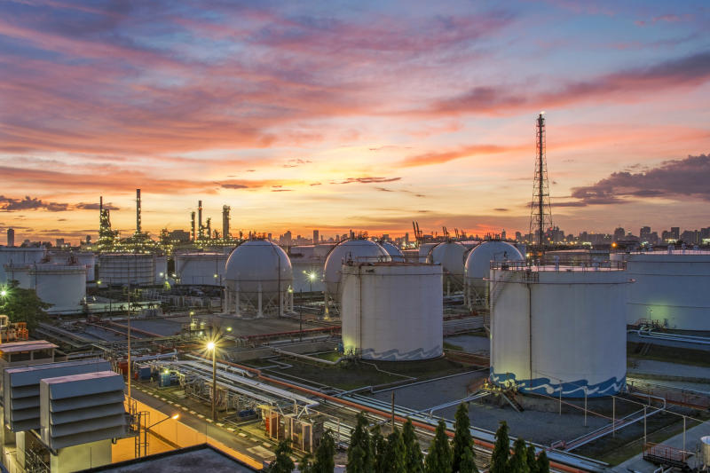 An oil refinery with a sunset in the background.