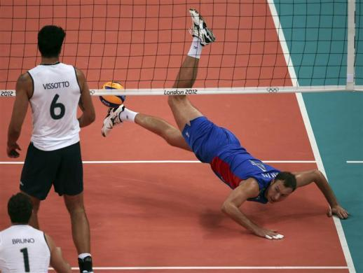 Russia's Taras Khtey (R) falls to the ground after failing to save a point as Brazil's Bruno Rezende (L) and Leandro Vissoto Neves look on during their men's Group B volleyball match against Brazil at the London 2012 Olympic Games at Earls Court July 31, 2012.