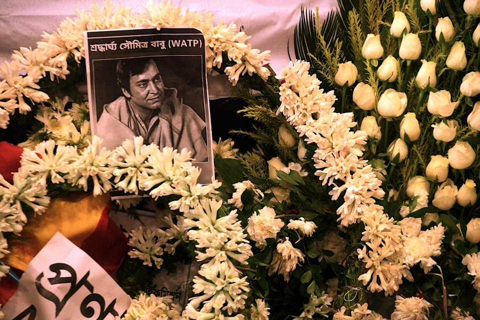 A picture of late Indian actor Soumitra Chatterjee is seen on garlands placed next to his body during his funeral in Kolkata.