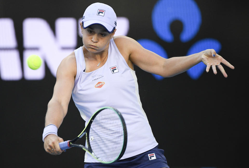 Australia's Ash Barty hits a backhand return to Russia's Ekaterina Alexandrova during their third round match at the Australian Open tennis championship in Melbourne, Australia, Saturday, Feb. 13, 2021.(AP Photo/Andy Brownbill)