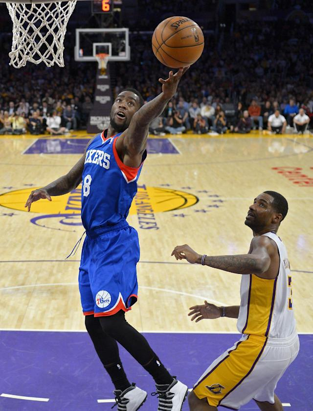 Philadelphia 76ers guard Tony Wroten, left, puts up a shot as Los Angeles Lakers forward Shawne Williams defends during the first half of an NBA basketball game, Sunday, Dec. 29, 2013, in Los Angeles. (AP Photo/Mark J. Terrill)