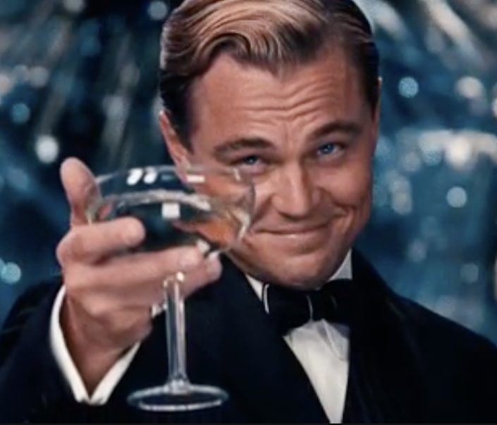 """Leonardo DiCaprio in """"The Great Gatsby"""" holding up a champagne glass in celebration"""