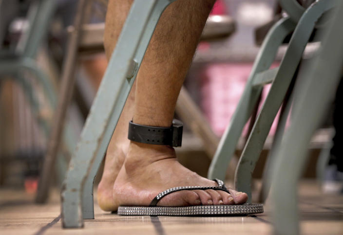 "<span class=""s1"">A migrant parent wears an ankle monitor bracelet above his donated flip-flops at the Annunciation House in El Paso, Texas, on June 26. (Photo: Matt York/AP)</span>"