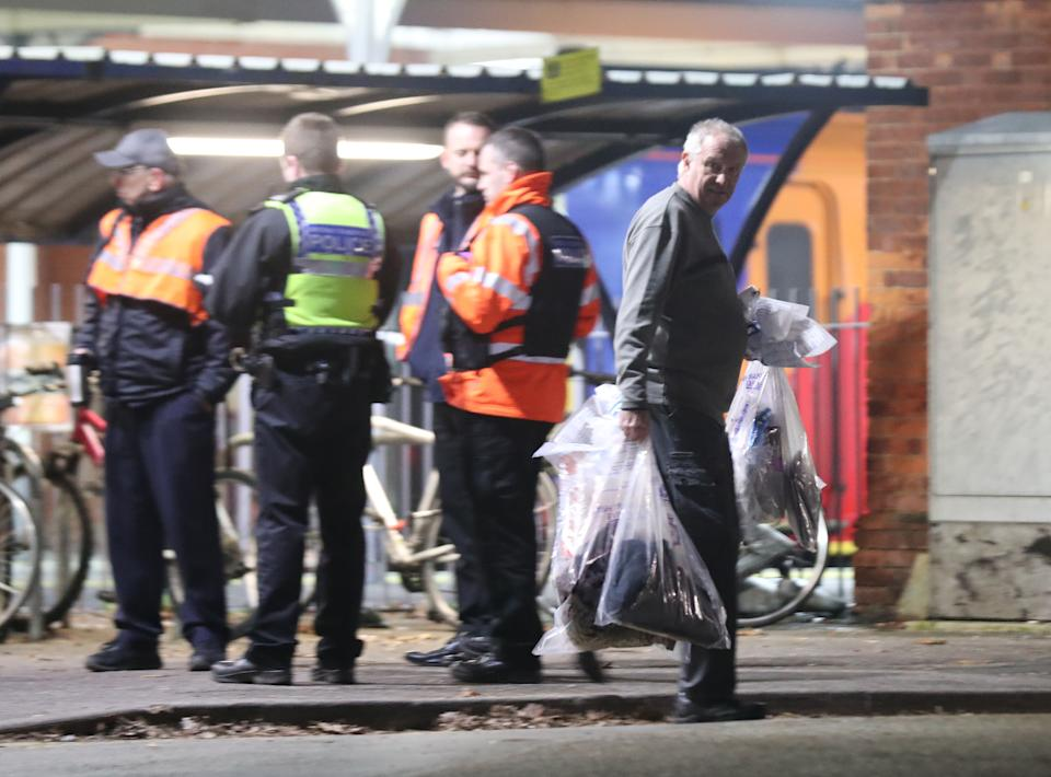 A forensics officer removes items at Horsley station near Guildford, Surrey, after a murder inquiry was launched following the stabbing of a man on board a train in Surrey.