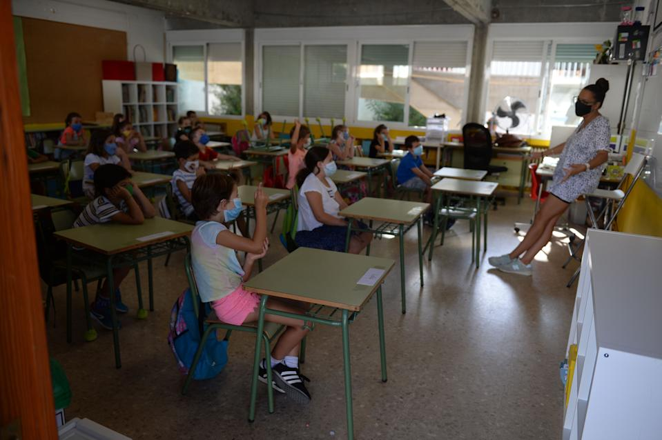 "Children sit on a classroom on the first day of school at ""Colegio Aljarafe S.C.A."" in Mairena del Aljarafe, near Seville, on September 10, 2020. - Spain, that passed the landmark figure of 500,000 coronavirus infections, had largely gained control over its outbreak by imposing one of the world's toughest lockdowns, but infections have surged since the restrictions were fully removed at the end of June. (Photo by CRISTINA QUICLER / AFP) (Photo by CRISTINA QUICLER/AFP via Getty Images)"