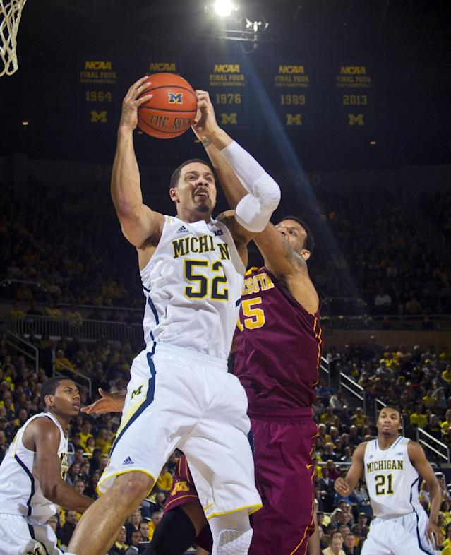 Michigan forward Jordan Morgan (52) grabs a rebound from Minnesota forward Maurice Walker (15) during the second half of an NCAA college basketball game at Crisler Center in Ann Arbor, Mich., Saturday, March 1, 2014. Michigan won 66-56. (AP Photo/Tony Ding)