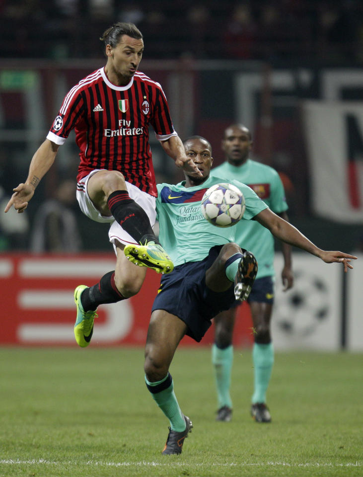 AC Milan forward Zlatan Ibrahimovic, of Sweden, left, challenges for the ball with Barcelona midfielder Seydou Keita, of Mali during a Champions League, Group H soccer at the San Siro stadium in Milan, Italy, Wednesday, Nov.23, 2011. (AP Photo/Luca Bruno)