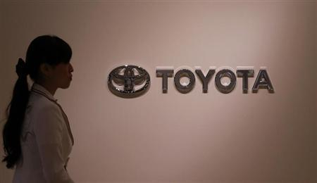 Woman walks past Toyota Motor's logo at the company showroom in Nagoya