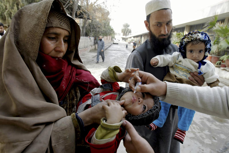 "In this Feb. 2, 2014 photo, a health worker vaccinates a child against polio, in Peshawar, Pakistan. Pakistan's beleaguered battle to eradicate polio is threatening a global, multi-billion dollar campaign to wipe out the disease worldwide. Because of Pakistan, the virus is spreading to countries that were previously polio free, say U.N. officials. ""The largest poliovirus reservoir of the world,"" is in Peshawar, the capital of Pakistan's northwest Khyber Pukhtunkhwa province, which borders Afghanistan, according to the World Health Organization. (AP Photo/Mohammad Sajjad)"