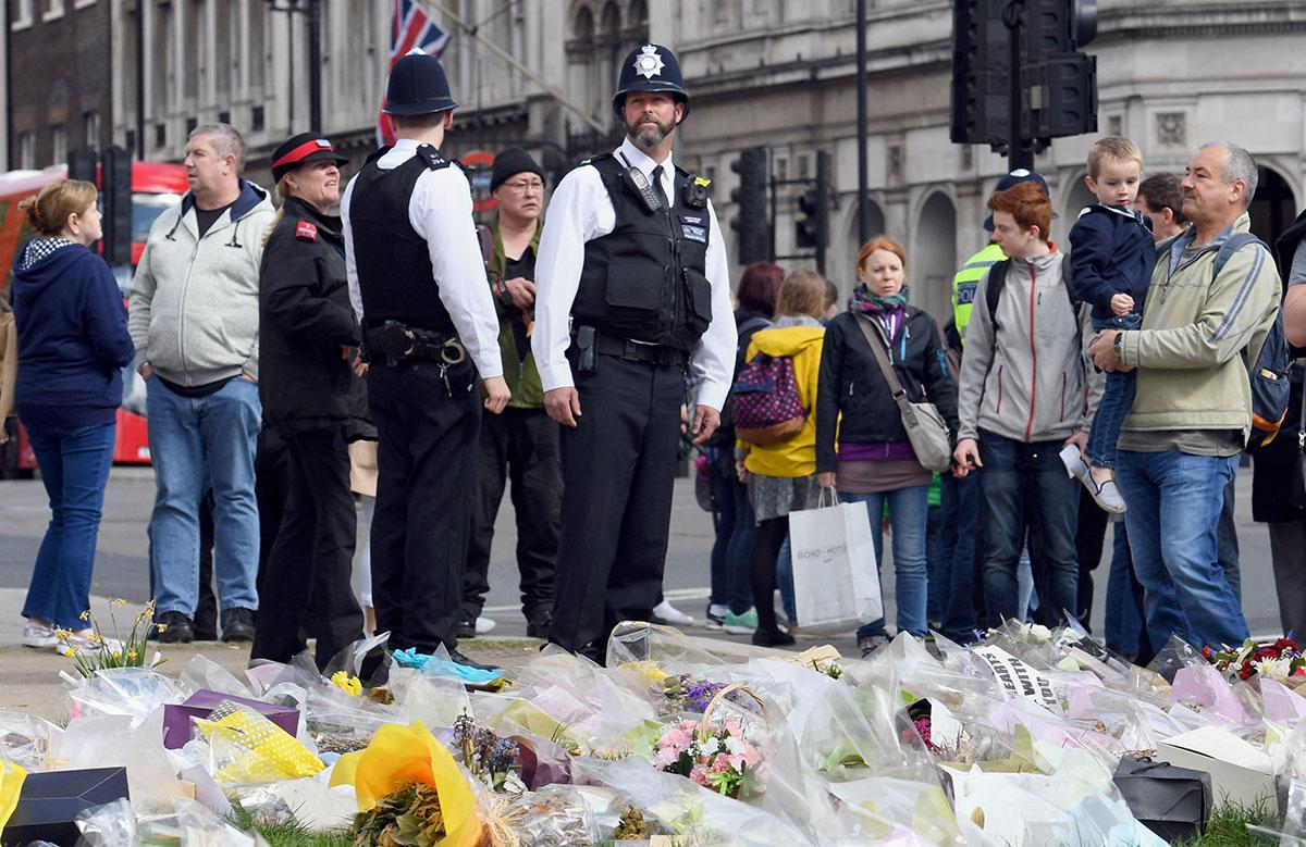 <p>Police officers stand next to the floral tributes left for PC Palmer close to the spot where he was killed. (PA Images) </p>
