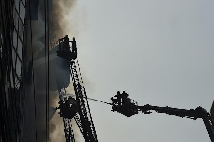 Bangladeshi firefighters on ladders work to extinguish a blaze in an office building in Dhaka on March 28, 2019. (Photo: Munir Uz Zaman/AFP/Getty Images)