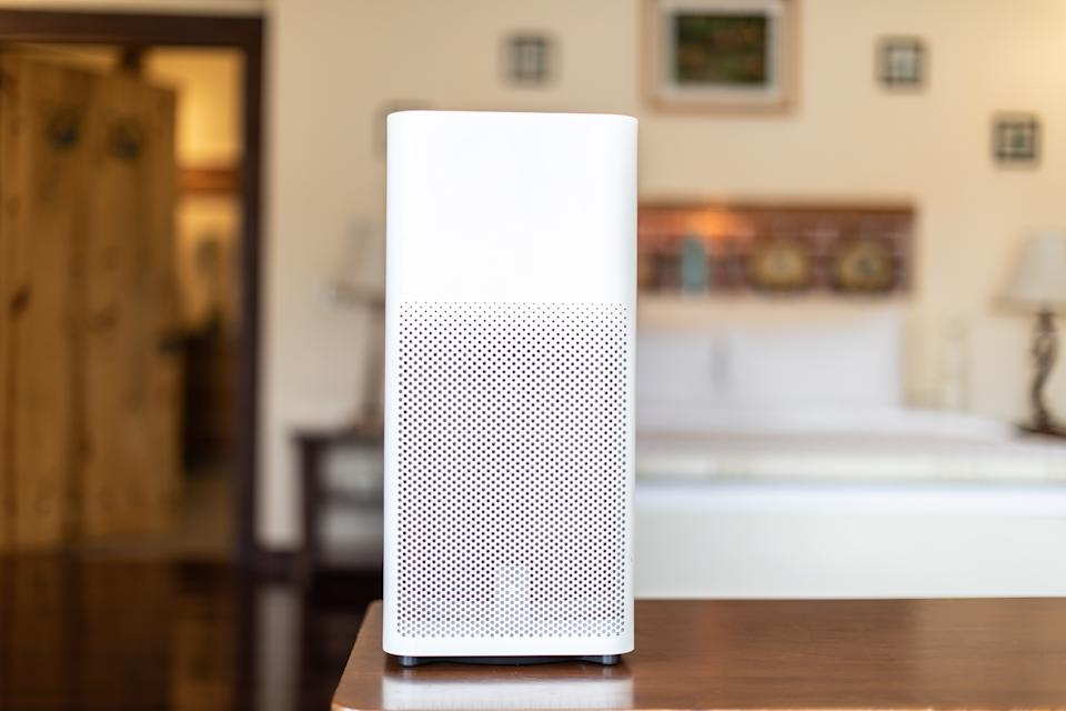 Air purifier in cozy white bedroom for filter and cleaning removing dust PM2.5 HEPA and virus in home,for fresh air and healthy Wellness life,Air Pollution Concept