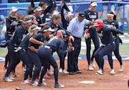 <p>YOKOHAMA, JAPAN - JULY 26: Kelsey Stewart #7 of Team United States jumps on home plate as the umpire and her teammates watch her score the winning run after Stewart hit a walk-off home run in the seventh inning against Team Japan during softball opening round on day three of the Tokyo 2020 Olympic Games at Yokohama Baseball Stadium on July 26, 2021 in Yokohama, Kanagawa, Japan. Team United States defeated Team Japan 2-1. (Photo by Yuichi Masuda/Getty Images)</p>