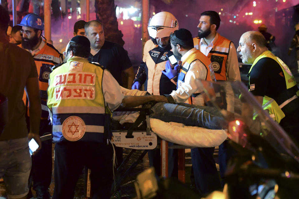 Israeli medics evacuate a wounded man after a rocket fired from the Gaza Strip hit the central Israeli town of Holon, near Tel Aviv, Tuesday, May 11, 2021. (AP Photo/Avshalom Sassoni)