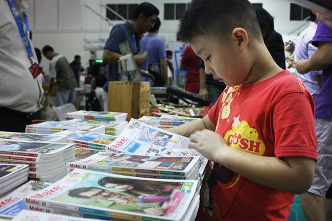 A young visitor browses through a copy of MAKE magazine, a guide on DIY projects