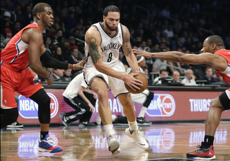 Two Los Angleles Clipper defenders try to stop a driving Brooklyn Nets guard Deron Williams (8) in the first half of their NBA basketball game at the Barclays Center, Thursday, Dec. 12, 2013, in New York. (AP Photo/Kathy Willens)