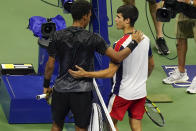 Felix Auger-Aliassime, of Canada, left, talks to Carlos Alcaraz, of Spain, after a quarterfinals match at the U.S. Open tennis tournament, Tuesday, Sept. 7, 2021, in New York. Auger-Aliassime has reached his first Grand Slam semifinal at the U.S. Open after 18-year-old Alcaraz stopped playing in the second set shortly after a visit from the trainer. (AP Photo/Frank Franklin II)