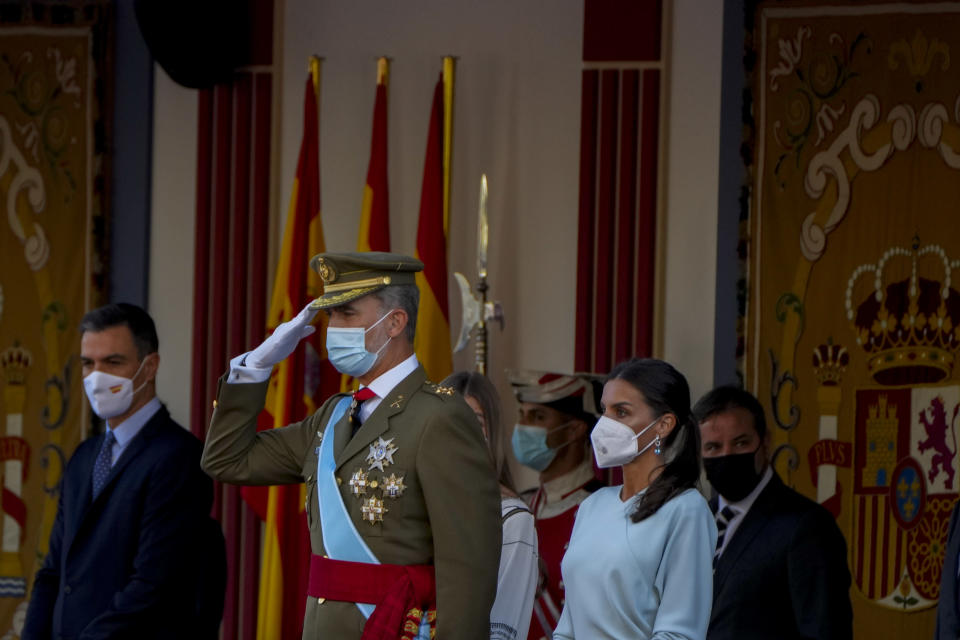 Spain's King Felipe, center, salutes next to Queen Letizia, right, during a military parade to celebrate a holiday known as 'Dia de la Hispanidad' or Hispanic Day in Madrid, Spain, Tuesday, Oct. 12, 2021. Spain commemorates Christopher Columbus' arrival in the New World and also Spain's armed forces day. (AP Photo/Manu Fernandez)