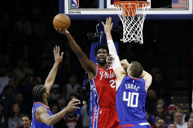 Philadelphia 76ers' Joel Embiid, center, goes up for a shot between Los Angeles Clippers' Ivica Zubac, right, and Kawhi Leonard during the first half of an NBA basketball game, Tuesday, Feb. 11, 2020, in Philadelphia. (AP Photo/Matt Slocum)