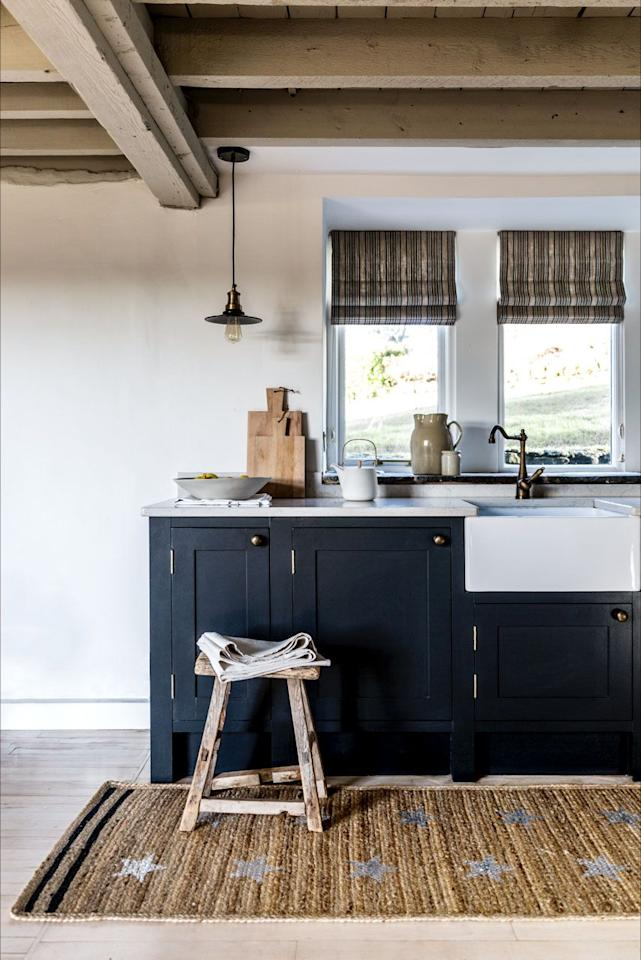 """<p>Wooden beams and the handmade rug make this countryside kitchen feel incredibly rustic. The dark pop of blue brings an added charm.<strong><br></strong></p><p><strong>READ MORE:</strong> <a href=""""https://www.housebeautiful.com/uk/lifestyle/shopping/a26780618/smeg-fridge-colours/"""">Smeg debuts three beautiful new finishes to its fridges</a></p><p>• Shop the look at <a href=""""https://www.tateanddarby.com/"""" target=""""_blank"""">Tate & Darby</a></p>"""
