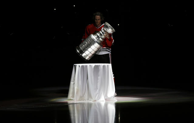 In this Oct. 1, 2013, photo, Chicago Blackhawks defenseman Duncan Keith carries out the Stanley Cup during a banner raising ceremony before an NHL hockey game between the Blackhawks and the Washington Capitals in Chicago. In an Associated Press and Canadian Press survey of player representatives from all 31 NHL teams, 48 percent favor changing the current divisional playoff format. (AP Photo/Nam Y. Huh)