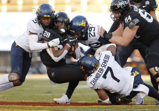 Iowa State running back Breece Hall, center, fights for yards as he is swarmed by West Virginia cornerback Dreshun Miller, left, safety Sean Mahone, right, and West Virginia linebacker Josh Chandler-Semedo, bottom, during the first half of an NCAA college football game, Saturday, Dec. 5, 2020, in Ames, Iowa. (AP Photo/Matthew Putney)