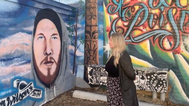 Demi Wilson looks at a portrait of her late brother Bronson. The mural was painted by  Red Deer artist Jesse Gouchey.