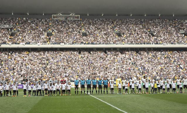 Corinthians's and Figueirense players listen the national anthem prior to a Brazilian soccer league match at the Itaquerao, the still unfinished stadium that will host the World Cup opener match between Brazil and Croatia on June 12, in Sao Paulo, Brazil, Sunday, May 18, 2014. Only 40,000 tickets were put on sale for Corinthians' match against Figueirense because some of the 20,000 temporary seats needed for the World Cup opener are still being installed. (AP Photo/Andre Penner)