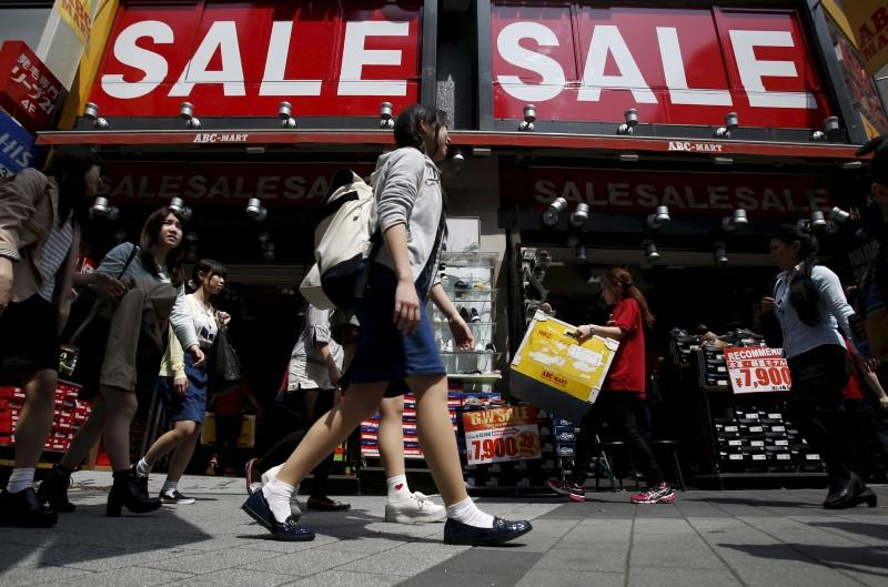 File photo shows a shop clerk carrying a box of shoes under sale signboards at a shoes retail store at a shopping district in Tokyo