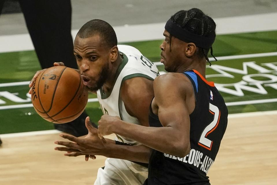 Milwaukee Bucks' Khris Middleton tries to drive past Oklahoma City Thunder's Shai Gilgeous-Alexander during the second half of an NBA basketball game Friday, Feb. 19, 2021, in Milwaukee. (AP Photo/Morry Gash)