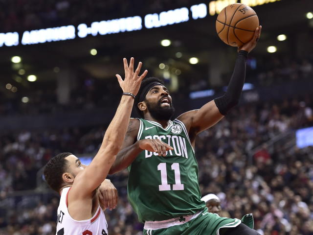 Boston Celtics guard Kyrie Irving (11) makes a basket as Toronto Raptors guard Fred VanVleet (23) defends during second-half NBA basketball game action in Toronto, Friday, Oct. 19, 2018. (Frank Gunn/The Canadian Press via AP)